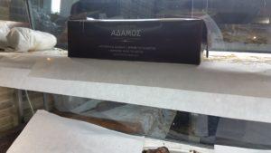 Auf der Schachtel für den Verkauf außer Haus steht: Grillhaus Adamos. Das Geschäft Ihres Vertrauens.  Hähnchen vom Spieß.  Milchlämmer. Gegrillte (Milch-)Spanferkel. Kokoretsi Kebap.