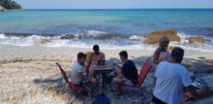 """Griechenlandklischee Nr. 27: junge Männer spielen """"Tavli"""" (Backgammon) am Strand von Kamari"""